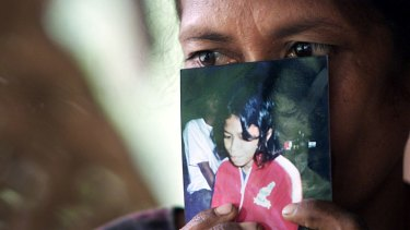 In this 2001 photo, Madalena Soares holds a photo of her 12-year-old daughter, Cesaltina, taken from her during the 1999 conflict and placed in a Java orphanage.
