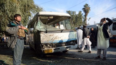 An Afghan security policeman stands guard near a damaged bus after a suicide attack in Nangarhar province east of Kabul, on Thursday.