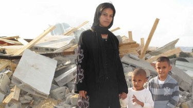 Rifa al-Oqbi and her two sons stand amid the rubble that was their home in the village of al-Qrain, in Israel's southern Negev Desert.