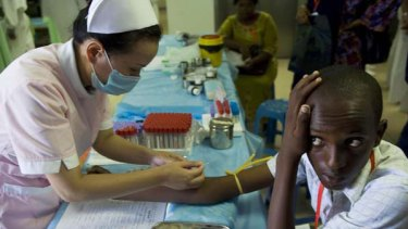 A Chinese nurse working onboard a hospital ship takes a blood sample from a Kenyan teenager in Mombasa.