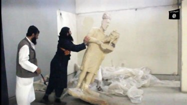 An IS jihadist pushes a statue over inside the Mosul museum in the northern Iraqi Governorate of Nineveh.