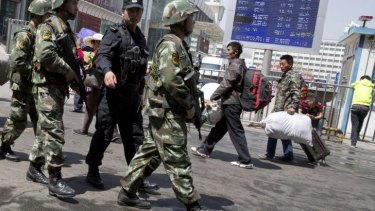 Armed Chinese paramilitary policemen march past the site of an explosion outside the Urumqi South Railway Station in Urumqi in northwest China in May.