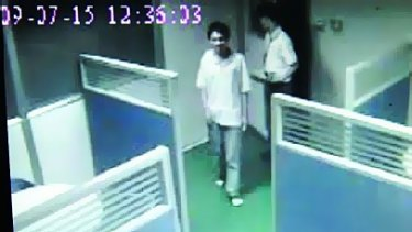 A video screen grab obtained by the Southern Metropolis Daily purporting to show Foxconn employee  Sun Danyong being let into a room to be questioned on July 15.   Photo is a video screen grab showing Sun Danyong being ushered into a room to be interviewed.