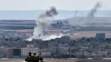 Kobane burns ... Turkish soldiers in a tank observe the Syrian town of Kobane  from a hill at the Turkish-Syrian border.