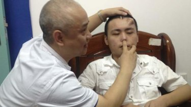 A doctor checks the infected and deformed nose of Xiaolian.