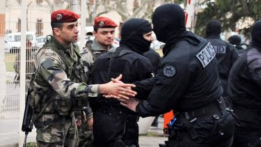 Relief ... a French member of the RAID special police forces unit shakes hands with a paratrooper.
