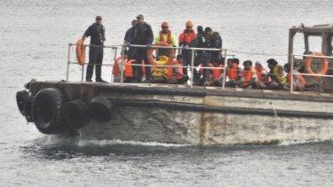 Asylum seekers rescued last week are taken to shore.