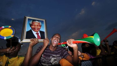 Supporters bearing a photograph of Nelson Mandela watch the opening game of the 2010 Soccer World Cup in South Africa.