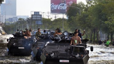 Thai military plow through the water into the flood zone in armored personnel carriers in Bangkok.