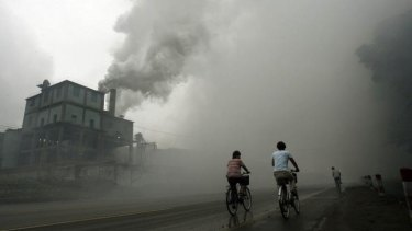 This 2006 file photo shows cyclists passing through thick pollution from a factory in Yutian, 100km east of Beijing, China.