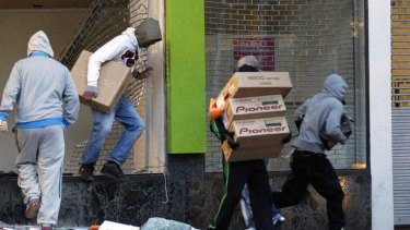 Looters carry boxes out of a home cinema shop.