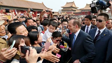 Prime Minister Tony Abbott greets excited tourists during his tour of the Forbidden City in Beijing.