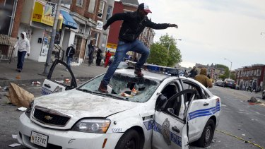 Rioter jumps on a damaged police department vehicle during clashes in Baltimore.