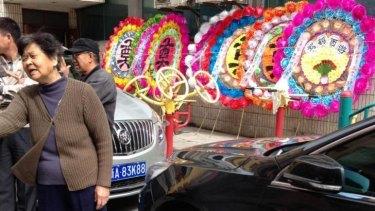 Locals in Urumqi's Gongyuan South Street prepare wreaths for slain relatives.