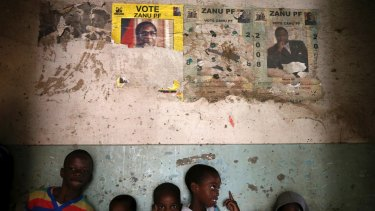 Children stand beneath posters from the 2008 Zanu Pf election campaign in the Mbara suburb of Harare on Friday November 17.