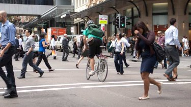 Anything goes ... a cyclist, pedestrians and a green light on a busy city street.