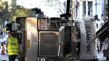 A truck carrying vacuum cleaners lies on its side after tipping over in Melbourne's CBD.