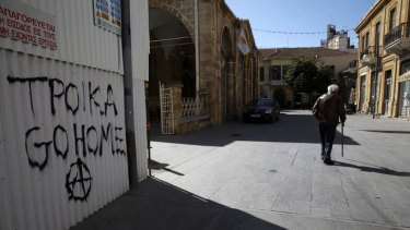 """A man walk past a graffiti which reads """"Troika go home"""" in the Cypriot capital of Nicosia on March 16, 2013. Eurozone finance ministers agreed on a bailout for Cyprus, the fifth international rescue package in three years of the debt crisis. AFP PHOTO/YIANNIS KOUTOGLOU"""