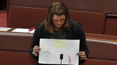 Greens Senator Sarah Hanson-Young tables drawings made by children held in the Manus Island detention centre.