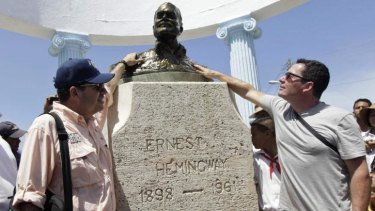 John Hemingway (left) and Patrick Hemingway (right), grandsons of the US author Ernest Hemingway, pay tribute to their grandfather at his statue in Cojimar village, Havana.