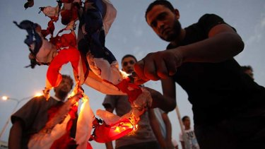 Libyan protesters burn a US flag.