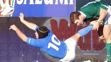 Australian-born five-eighth Kris Burton of Italy is tackled by Gordon D'Arcy.