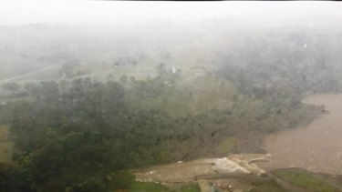 An aerial image of water flowing over the Jerrara Dam wall.