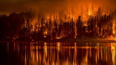 Fire approaches the shore of Bass Lake, California on Sunday.
