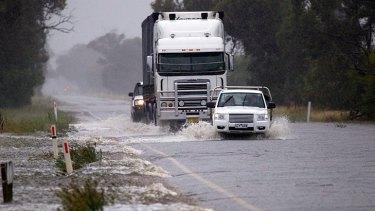 Trucks and cars battle to navigate floodwaters near Katamatite.