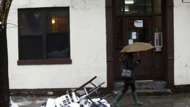 A woman walks past an apartment building that was raided by police.