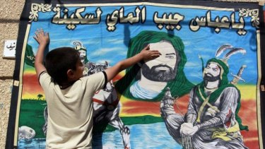 Holy days: An Iraqi child touches a banner bearing the portraits of Imam Hussein and his brother Abbas, both revered by Shiites. Hundreds of thousands of pilgrims from Iraq and neighbouring Iran will journey to Baghdad and Kerbala in the coming days to mark Ashura, a major Shiite religious event.
