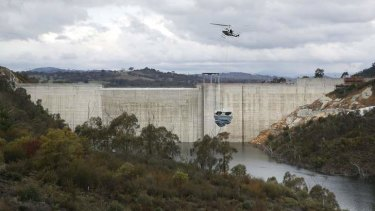 A helicopter lifts a destratification system into position at the Cotter Dam prior to completion.