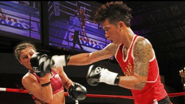 Thai boxer Usanakorn Kokietgym lands a blow on Australia's Susie Ramadan at the world title fight in Melbourne.