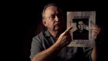 Arthur Budzinski points to a poster of his abuser, Father Lawrence Murphy.