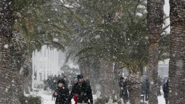 People walk along a snow covered street in Split, Croatia.
