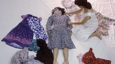 A still from Araya Rasdjarmrearnsook's video I'm Living features the artist dressing the body of an unknown dead woman.