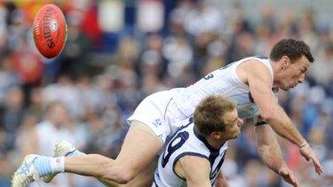 Kangaroo Brent Harvey leaps over Geelong's Darren Milburn  during yesterday's clash at Skilled Stadium.