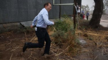 Prime Minister Tony Abbott dashes through a downpour after meeting graziers and community members at a property near Bourke NSW.