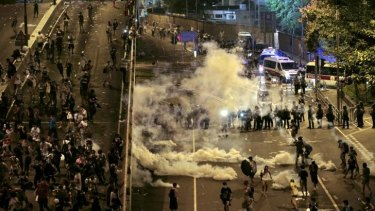 Riot police fire tear gas on student protesters occupying streets surrounding the government headquarters in Hong Kong.