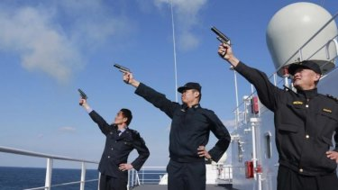Display: Chinese personnel fire their pistols to signal the start of a naval exercise as they stand on a vessel on the East China Sea.