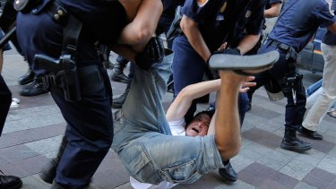 Police officers detain an protester while police try to dismantle a demonstration at Puerta del Sol Square in Madrid.