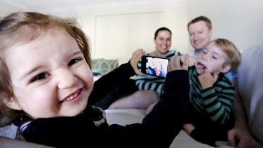 Antoinette and Kieron Maye, with their kids Zoe (2) and Patrick (5) who are playing with their parents iphones/androids/ipads at their home in Pemulwuy, Sydney.