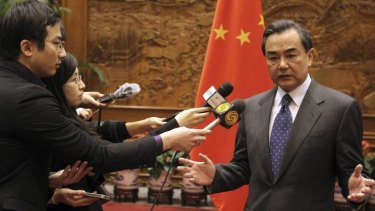 China's Foreign Minister Wang Yi speaks to journalists in front of a Chinese national flag after a meeting with Japan's ambassador to China at the Ministry of Foreign Affairs in Beijing.