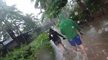 Australian tourists wade through rising waters at their Fiji resort.