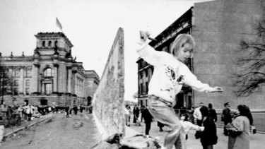 Tumbling down ... a girl plays on the rubble the day after East Germany began dismantling the Berlin Wall in February 1990.