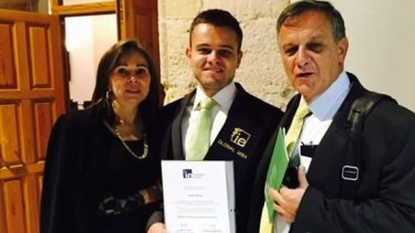 Javier Camelo with his parents at his graduation.
