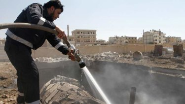 A firefighter hoses water on a burning gas station, which activists say was the result of shelling by forces loyal to Syria's President Bashar al-Assad in Raqqa province on Friday.