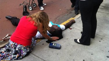 Crossfire … a passer-by tends the shooting victim Robert Asika outside the Empire State Building.