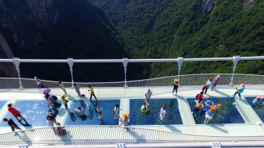 Visitors walk across a glass-floor suspension bridge in Zhangjiajie in southern China's Hunan Province.