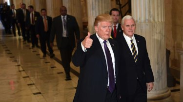 President Donald Trump gives a thumbs up as he walks with Vice-President Mike Pence as he leaves Capitol Hill in Washington on  Thursday
